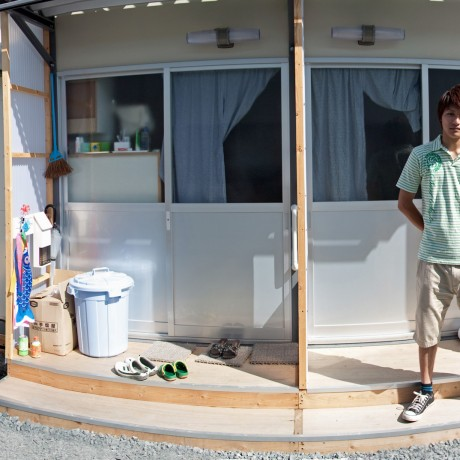 2011 - The youth community leader at an evacuation center in front of his family's temporary housing. The walls are so thin that normals level voices carry from one residence to another as if in the same room.